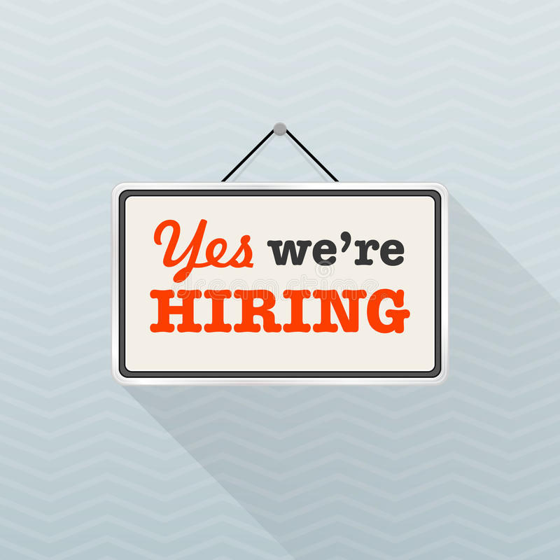 Simple white sign with text `Yes we`re hiring` hanging on a gray office wall. Human Resources, recruiting concept. royalty free illustration
