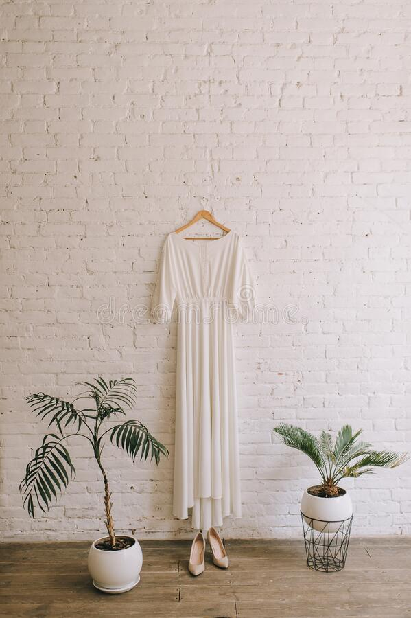 Simple white wedding dress on wall. Simple white wedding dress hanging on a white brick wall. White pots with plants royalty free stock images