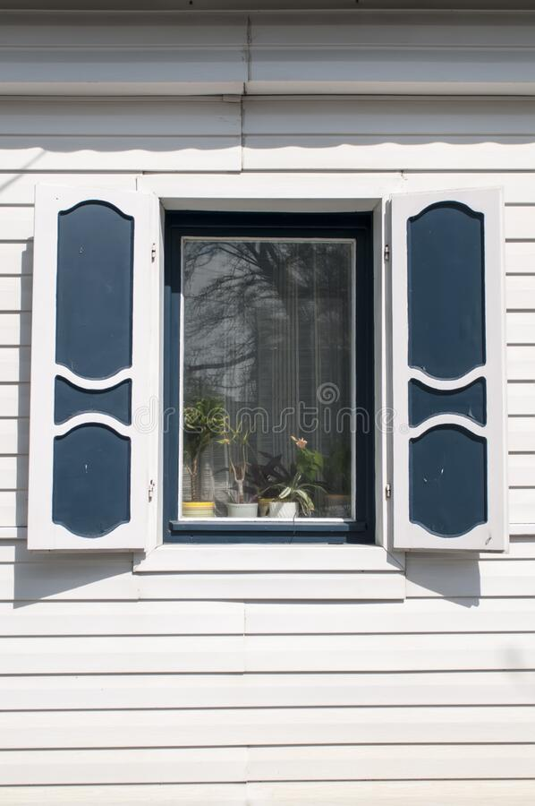 Simple white window with shutters on a blue wooden wall.  royalty free stock photography