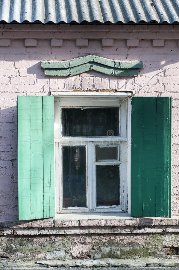 Simple white window with shutters on a green stone wall.  stock photos