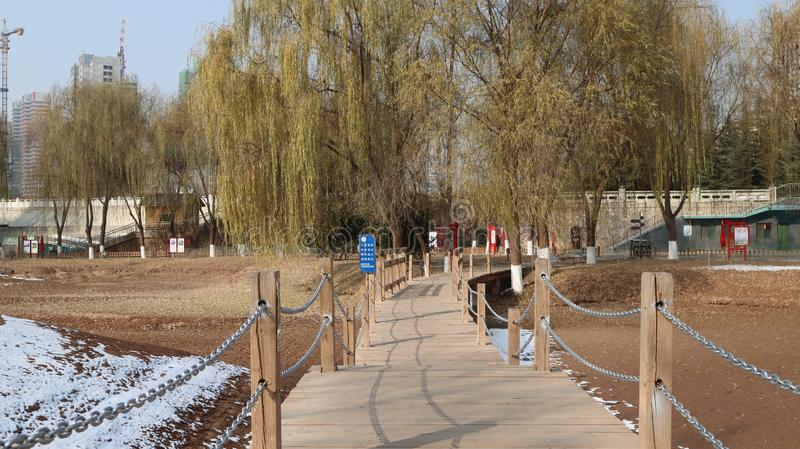 A simple wooden bridge in the park in winter stock photography