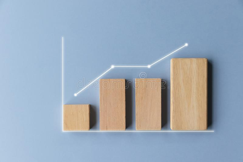 Simple wooden toy block financial bar chart graph with upward trend line on blue color background. Children`s nursery or retail business concept royalty free stock photo