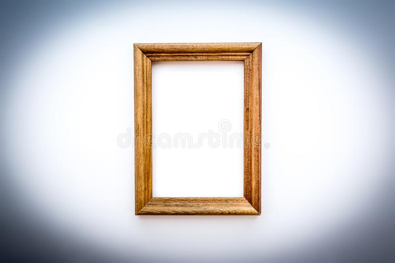 A simple wooden vertical photo frame close-up with an isolated white background inside with soft shadows.  stock photography