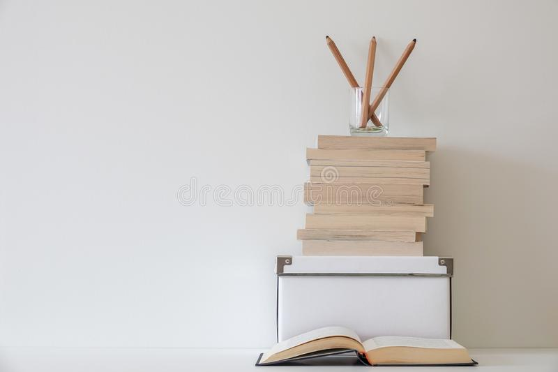 Simple workspace interior. Open book and pens in a glass. On a pile of books. Empty white copy space for text stock images