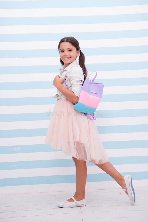 Simplemente cuteness La cara sonriente linda de la muchacha del niño lleva el bolso en hombro Equipo de moda del desgaste largo d imagen de archivo