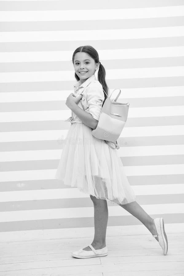 Simplemente cuteness La cara sonriente linda de la muchacha del niño lleva el bolso en hombro Equipo de moda del desgaste largo d foto de archivo libre de regalías