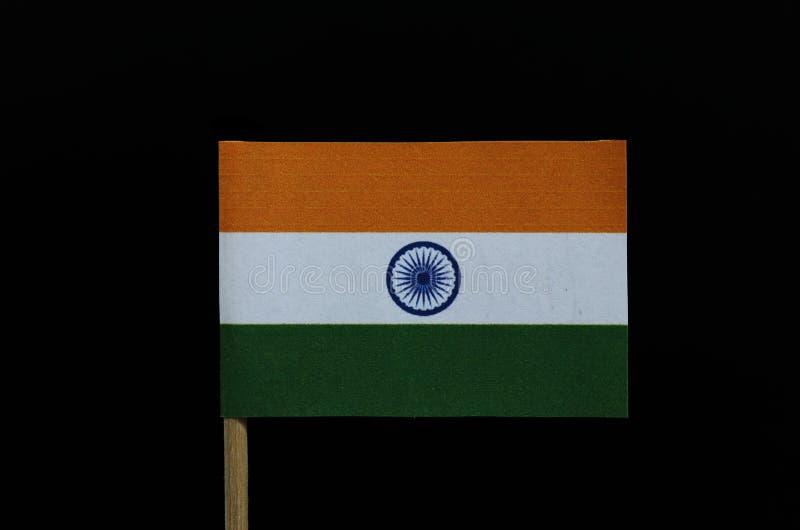 Simplemente y bandera oficial de la India en palillo en fondo negro Un triband horizontal del azafrán de la India, blanco, y de l imágenes de archivo libres de regalías