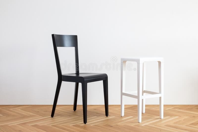 Simplistic black and white chair on a wooden floor in front of white background. Modern simplistic black and white chair on a wooden floor in front of white stock photography
