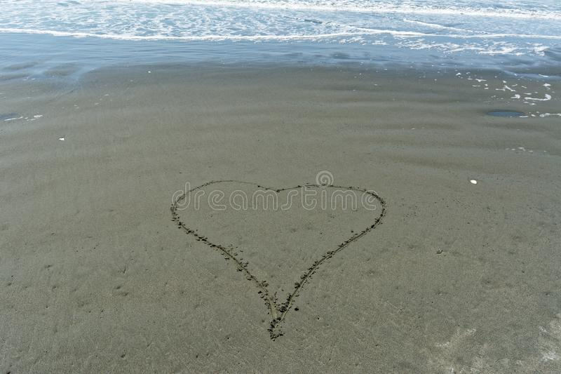 A simplistic love heart drawn by hand in the sand stock photography