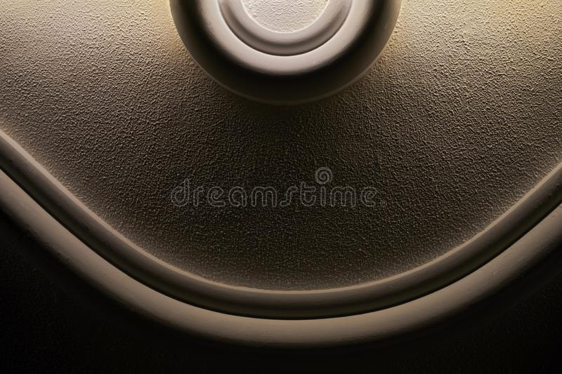 Simplistic roundish sculptured wall design in creme brown color and black background, with indirect lighting. Detailed close-up simplistic roundish sculptured stock images