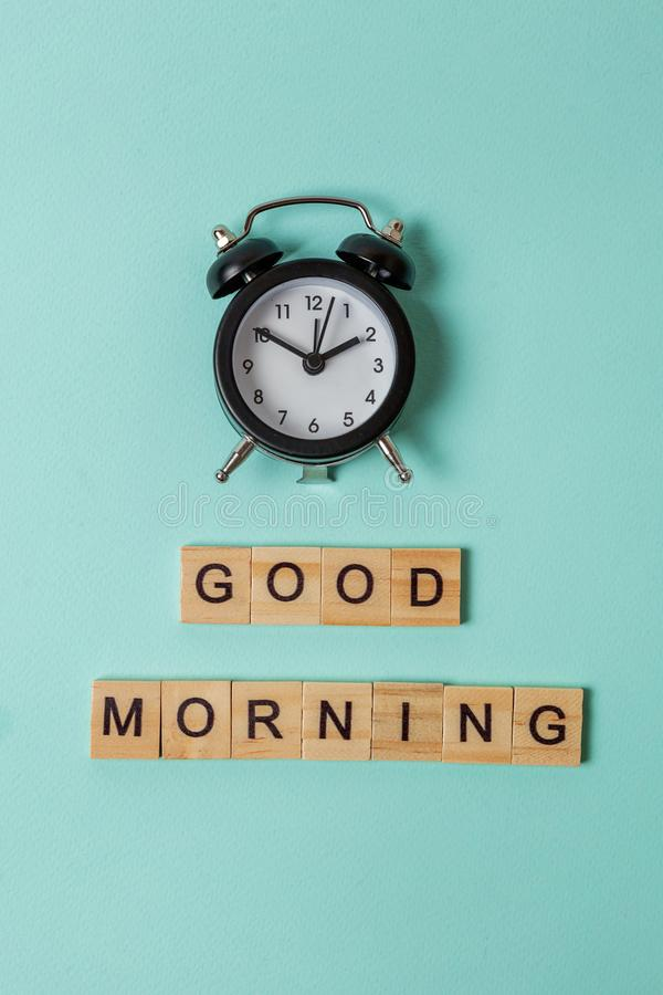 Alarm clock and Inscription GOOD MORNING letters word on blue background. Simply flat lay design alarm clock and Inscription GOOD MORNING letters word on blue royalty free stock images
