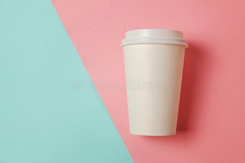 Paper cup of coffee on blue and pink background royalty free stock photography