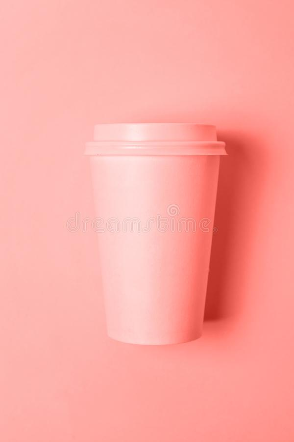 Simply flat lay design paper coffee cup colored in trendy color of year 2019 Living Coral background stock image