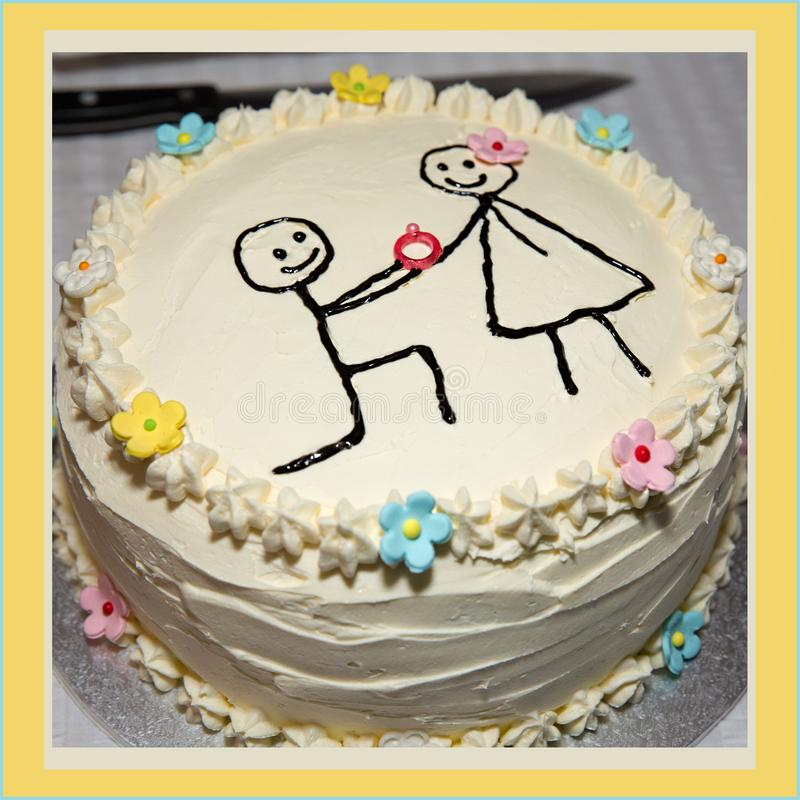 A Simple Engagement Cake. A simply iced engagement cake showing man proposing to woman with a ring stock photos