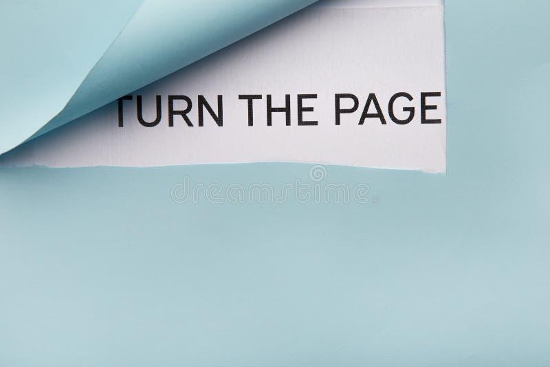 Simsen Sie Drehung die Seite auf Weißbuch hinter Blau gefalteter Ecke lizenzfreie stockbilder