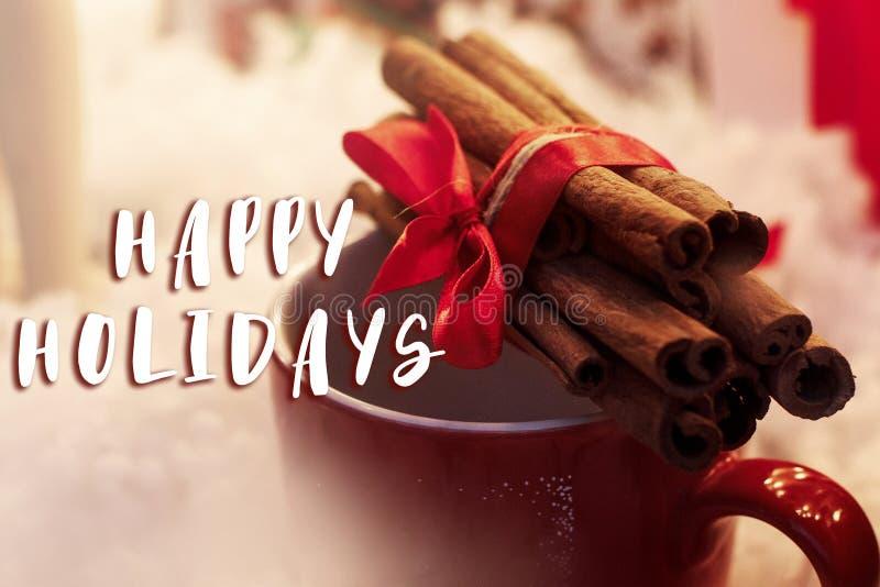 Simsen Sie frohe Feiertage Zeichen auf Zimtstangen mit Band auf rotem c lizenzfreie stockfotografie