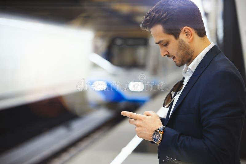 Simsende Mitteilung des attraktiven Geschäftsmannes im Handy beim Warten auf Zug in der Metro lizenzfreie stockfotos