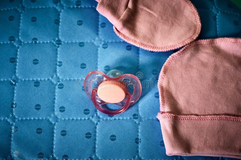 Simulacre, chapeau et chaussettes de bébé dans un berceau photos libres de droits