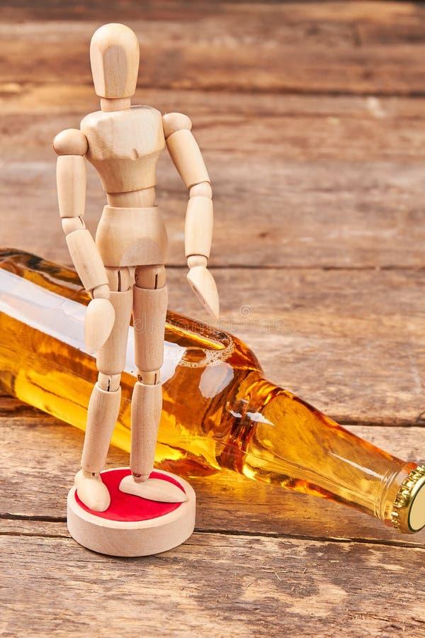 Simulacre en bois humain, bouteille d'alcool image libre de droits