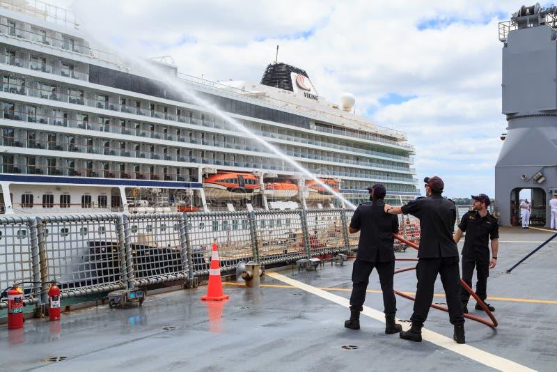 Simulacro de la manguera de bomberos en un barco de la Armada real de Nueva Zelanda imagenes de archivo