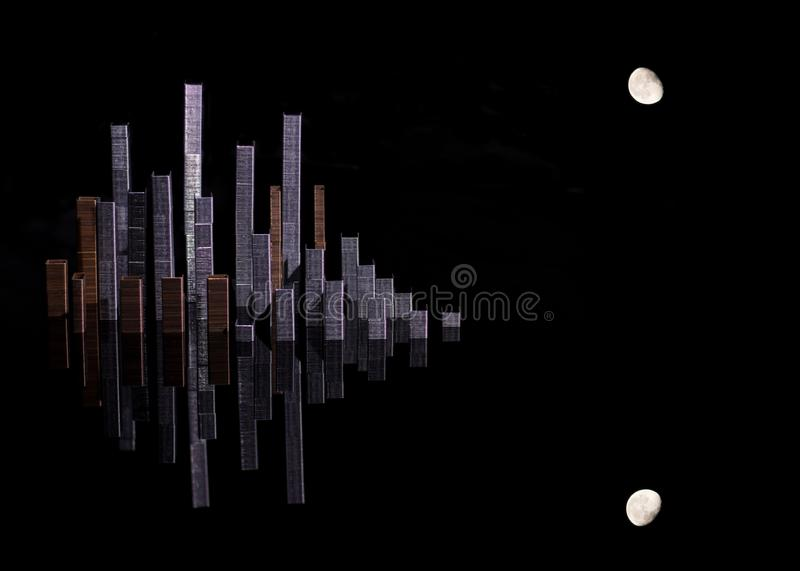 A simulated city skyline created with staples that form skyscrapers and the moon with a dark background and its reflection royalty free illustration
