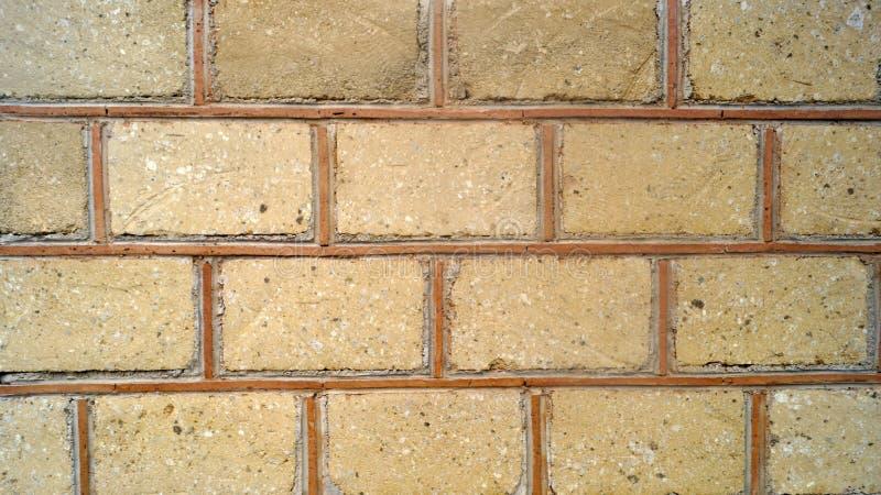 Simulerade sandfärgtegelstenar som delas av ockrabandväggen, texturerar bakgrund arkivbilder