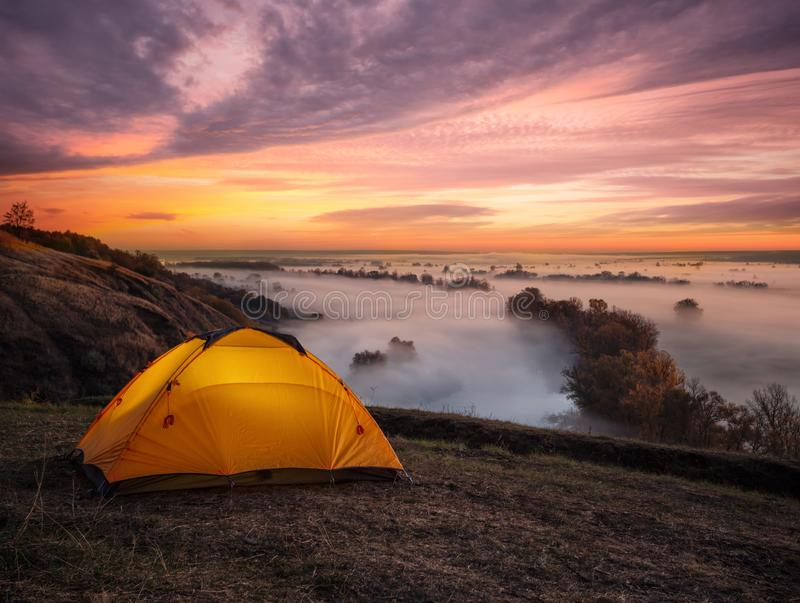 Sinaasappel die van binnenuit tent boven rivier bij zonsondergang wordt verlicht royalty-vrije stock foto's