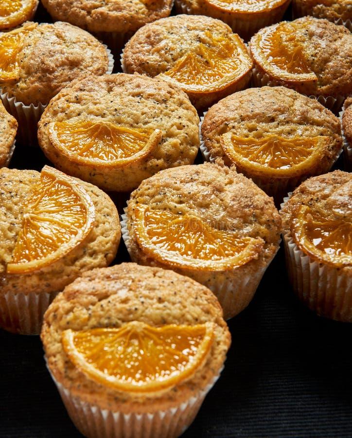 Sinaasappel en papaverzaadmuffins met oranje plakken worden verfraaid die stock foto