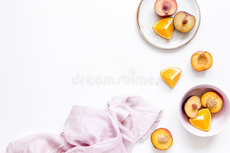 Sinaasappel en perzik de zomer zoet dessert op platen, wit achtergrond hoogste meningsmodel royalty-vrije stock afbeelding
