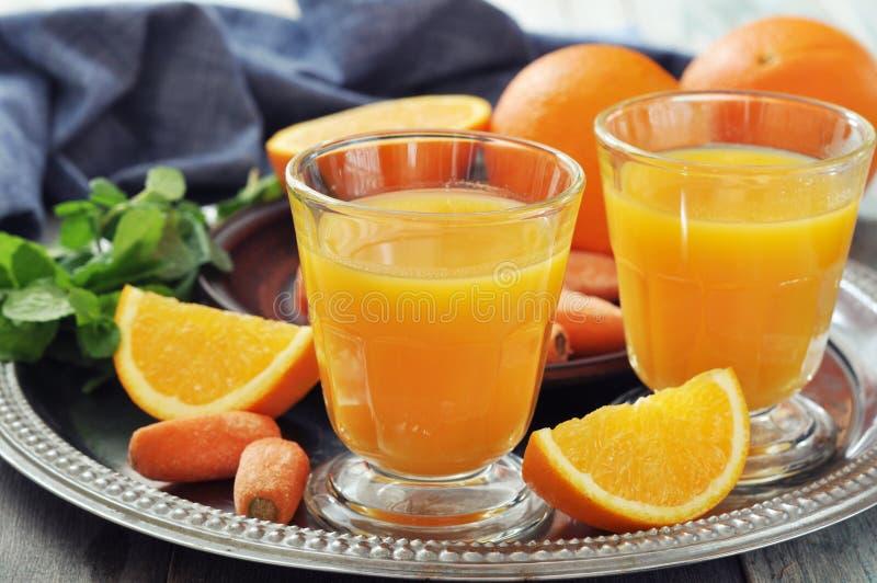 Sinaasappel en wortelsap stock foto