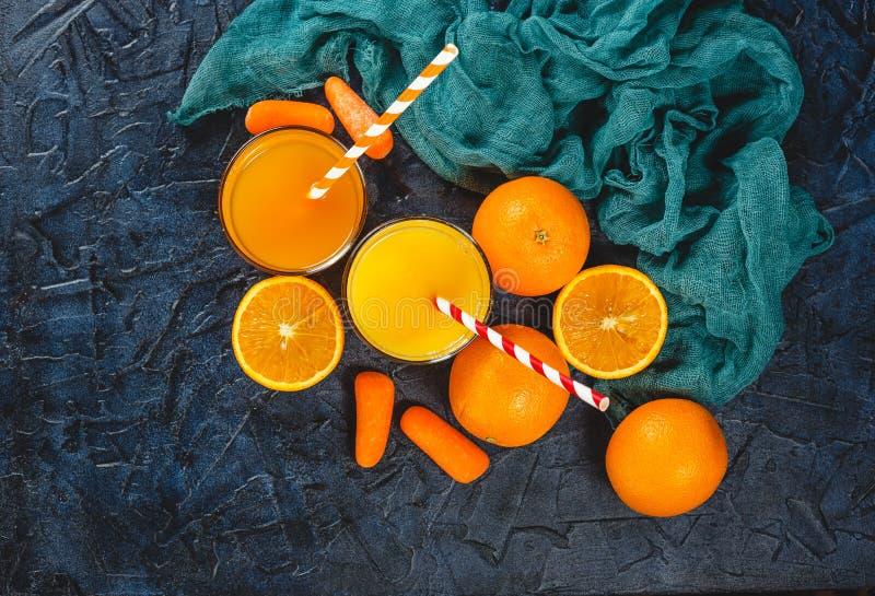 Sinaasappel en wortelsap stock afbeeldingen