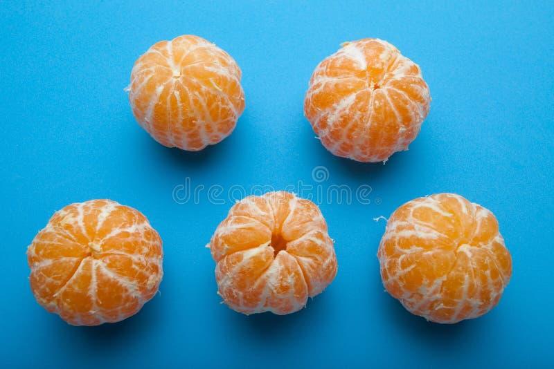Sinaasappel mandirins zonder schil op een blauwe achtergrond stock foto