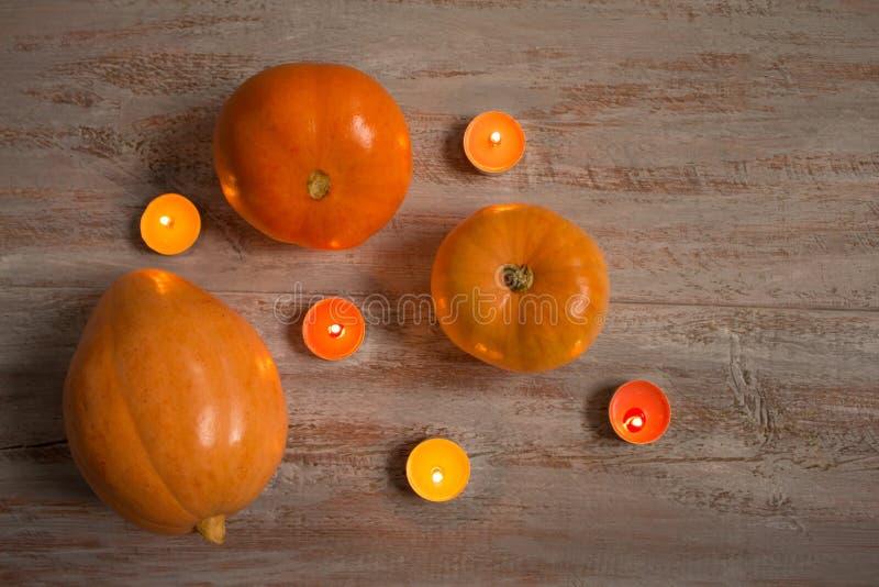 Sinaasappel pumkins met kleurrijke kaarsen op de houten raad royalty-vrije stock afbeelding