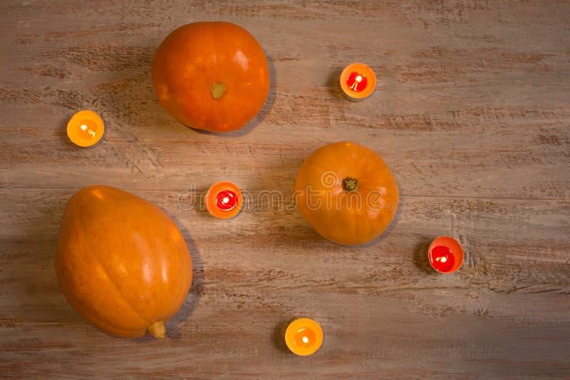Sinaasappel pumkins met kleurrijke kaarsen op de houten raad royalty-vrije stock foto's