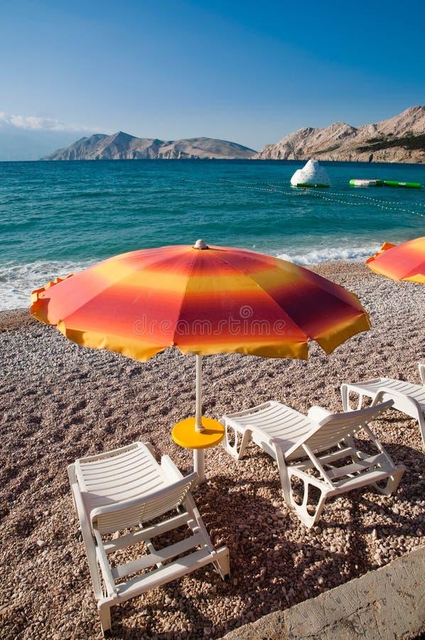 Sinaasappel sunshades en ligstoelen op Baska strand - Krk - Kroatië stock fotografie