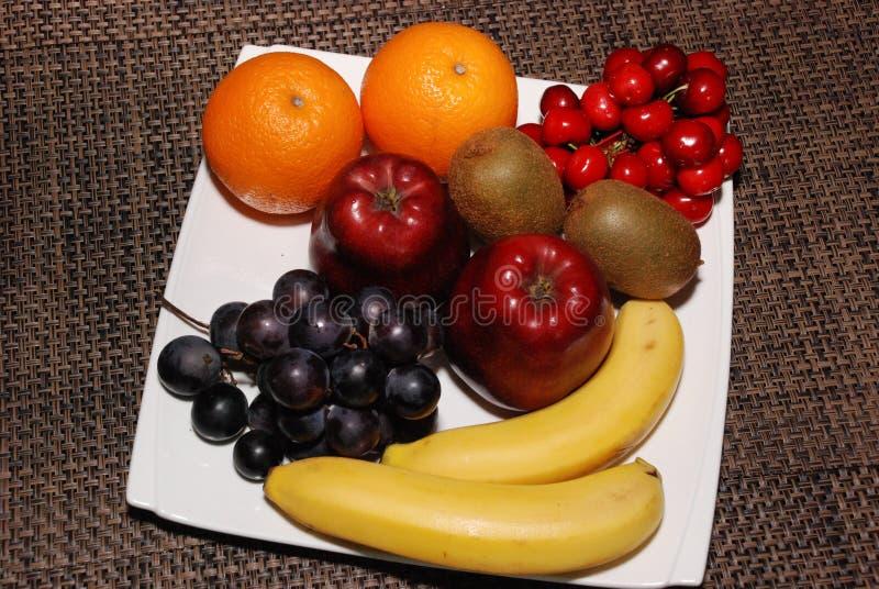 Sinaasappelen, appelen, druiven, kiwien, kersen, bananen op de witte plaat op de bruine lijst royalty-vrije stock foto's
