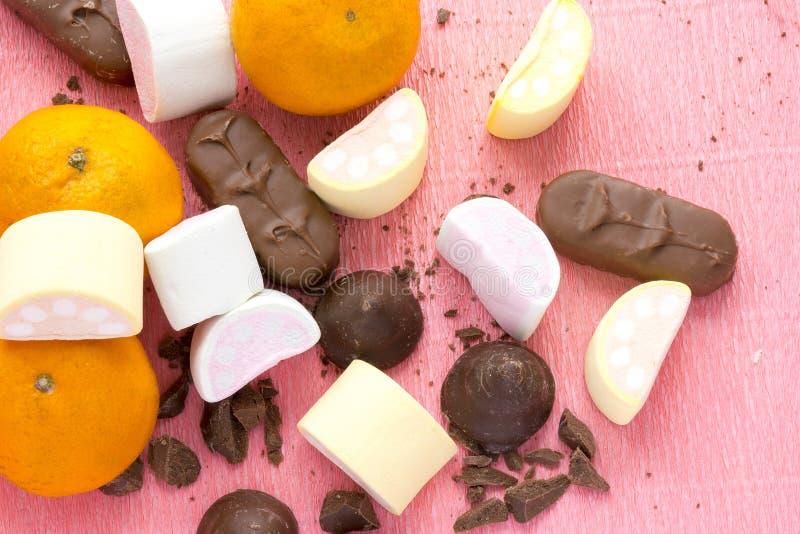Sinaasappelen, chocolade en zefier op roze achtergrond Het koken van eigengemaakte snoepjes stock afbeeldingen