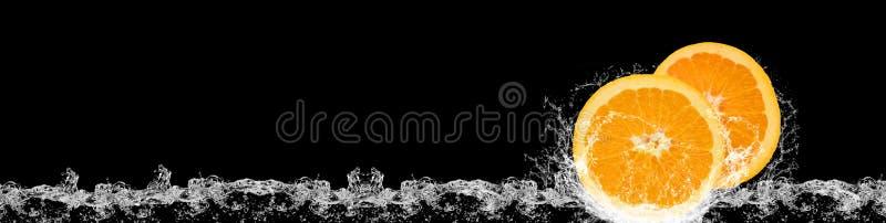 Sinaasappelen die in water op zwarte vallen stock afbeeldingen