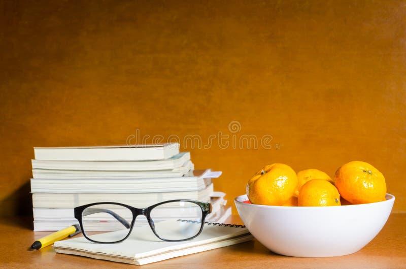 Sinaasappelen en glazen op notitieboekje en boeken op houten lijst stock foto's