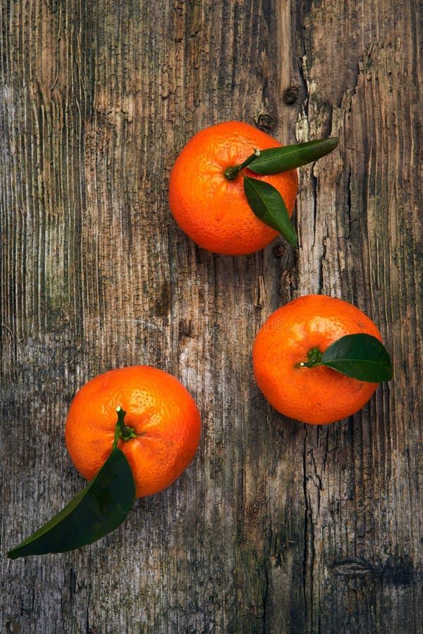 Sinaasappelen, mandarins, clementines, citrusvruchten met bladeren op houten achtergrond royalty-vrije stock afbeeldingen