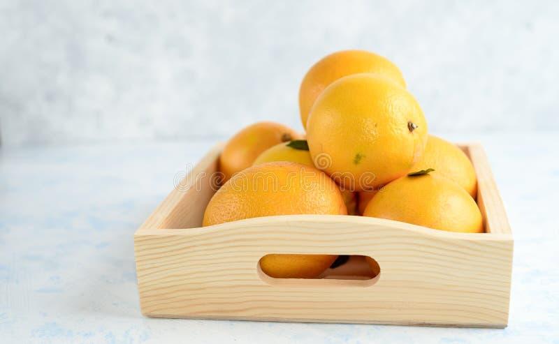 Sinaasappelen met bladeren in doos Op een blauwe lijst Vrije ruimte voor tekst royalty-vrije stock fotografie