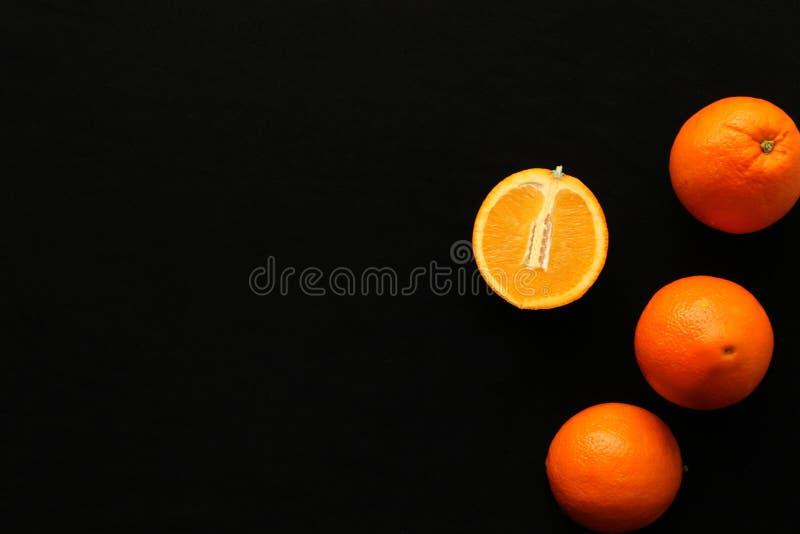 Sinaasappelen op de zwarte achtergrond stock afbeelding