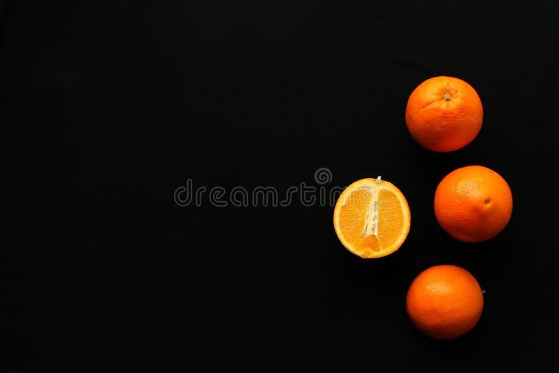 Sinaasappelen op de zwarte achtergrond stock foto's