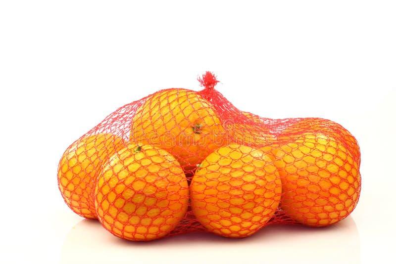 Sinaasappelen in rode plastic netto royalty-vrije stock foto's