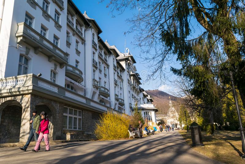 Sinaia Rumänien - mars 09, 2019: Folket tycker om går i Sinaia Central Park gränder längs sidoPalace Hotel i Prahova County, arkivfoto