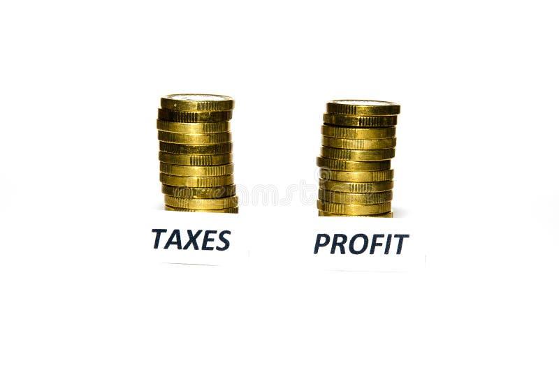 Impostos e sinais do lucro em pilhas da moeda fotografia de stock royalty free