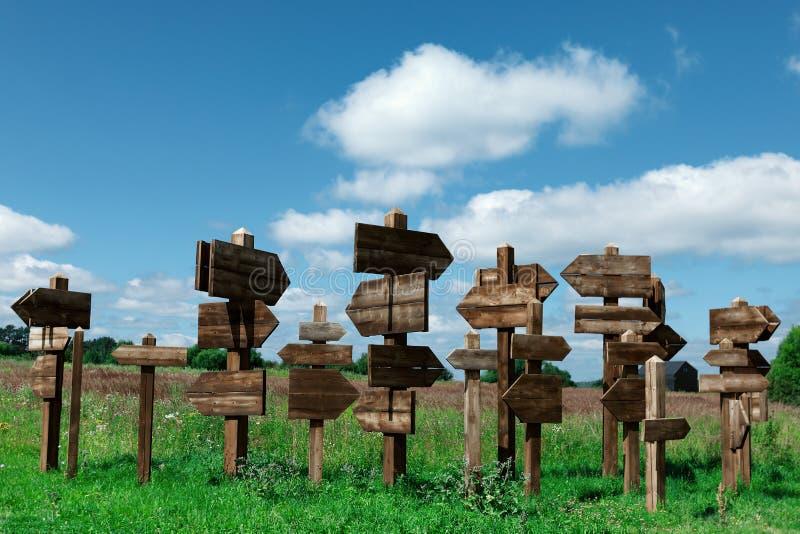 Sinais de madeira que indicam o sentido imagem de stock