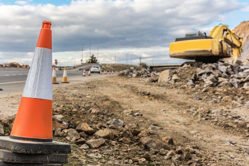 Sinais dos trabalhos e do perigo em uma extensão de uma estrada imagens de stock