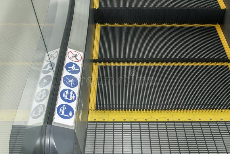Sinais em uma escada rolante, sinais de aviso imagem de stock