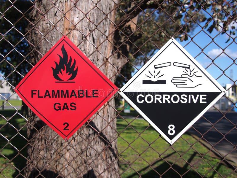 Sinais para líquidos inflamáveis e substâncias corrosivas em uma cerca foto de stock